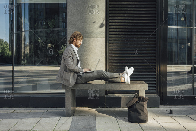 Male professional using laptop while sitting on bench with cross legs at downtown