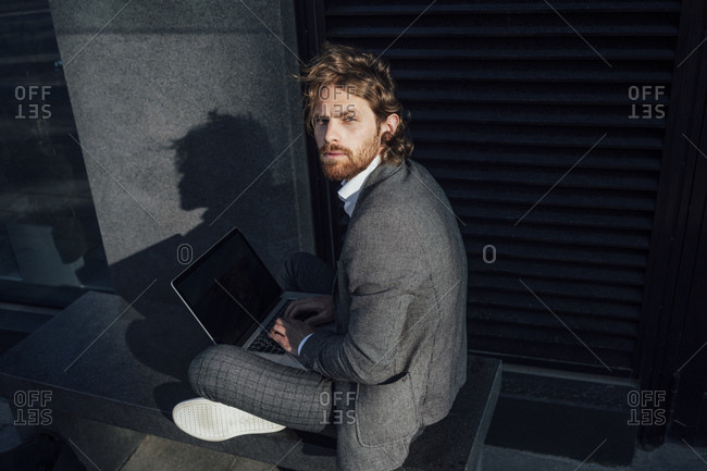 Confident young businessman with laptop sitting on bench at financial district in city