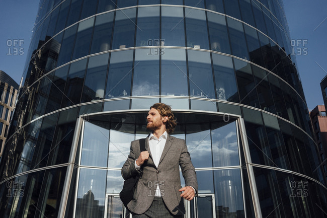 Young male entrepreneur looking away while walking against modern office building at financial district