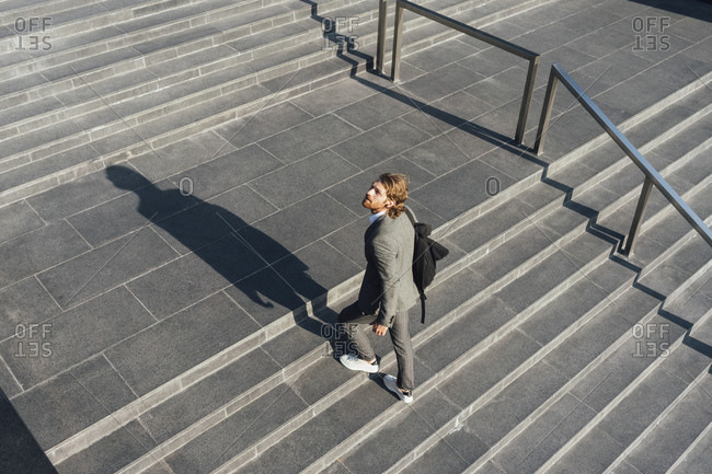 Male entrepreneur with bag moving up on staircase while looking away in downtown during sunny day