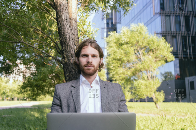 Confident handsome businessman sitting with laptop against tree at financial district