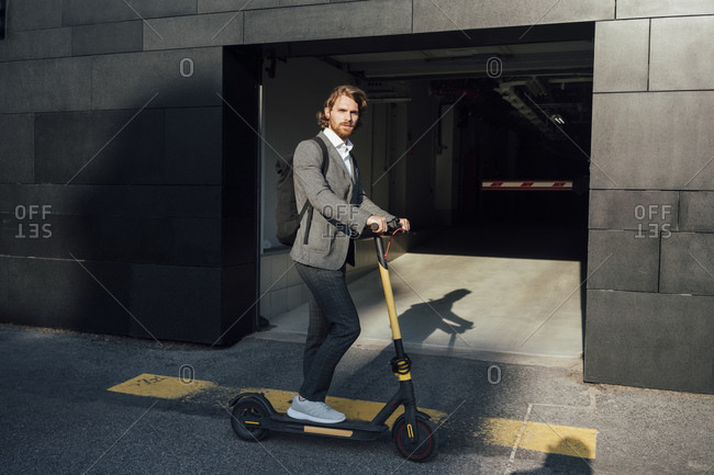 Confident businessman riding electric push scooter to commute in downtown