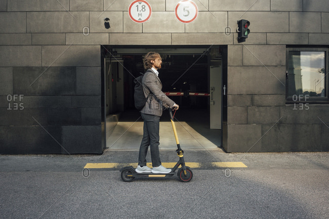 Young male professional riding electric push scooter to commute in downtown