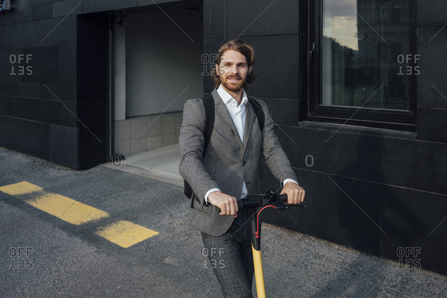 Confident handsome male entrepreneur riding electric push scooter to commute in downtown