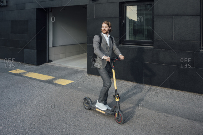Young businessman riding electric push scooter to commute in city