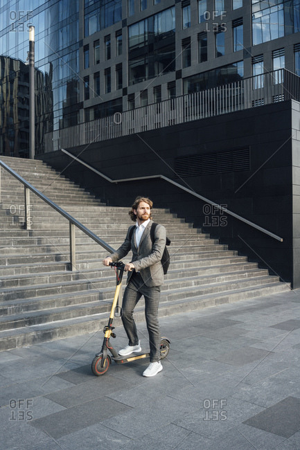 Male commuter riding electric push scooter by staircase in city