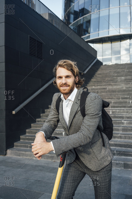 Confident young male entrepreneur leaning on push scooter against staircase in downtown