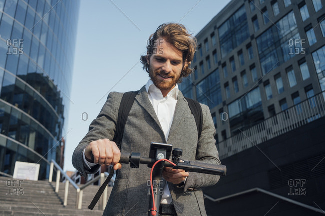 Male entrepreneur using mobile phone while standing with electric push scooter at downtown