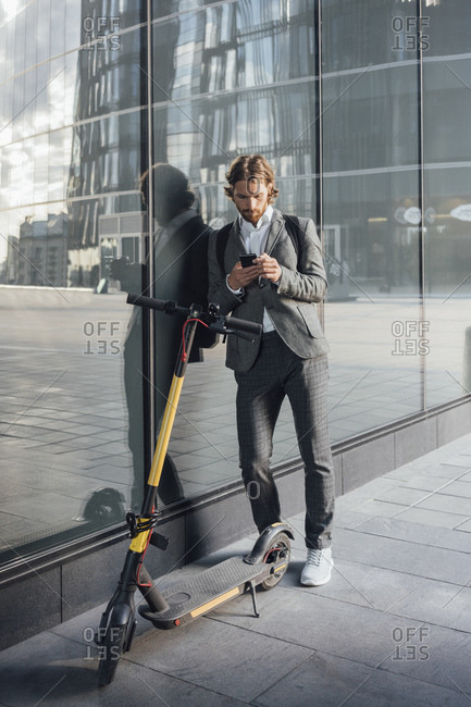 Young male commuter using smart phone while leaning on glass by electric push scooter in financial district