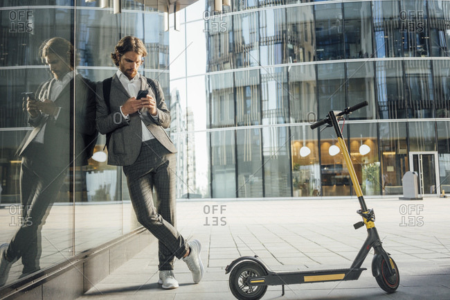Businessman using mobile phone while leaning on glass with reflection by electric push scooter in financial district