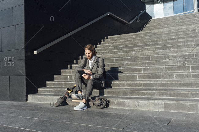 Businessman using digital tablet while sitting with electric push scooter on steps in financial district