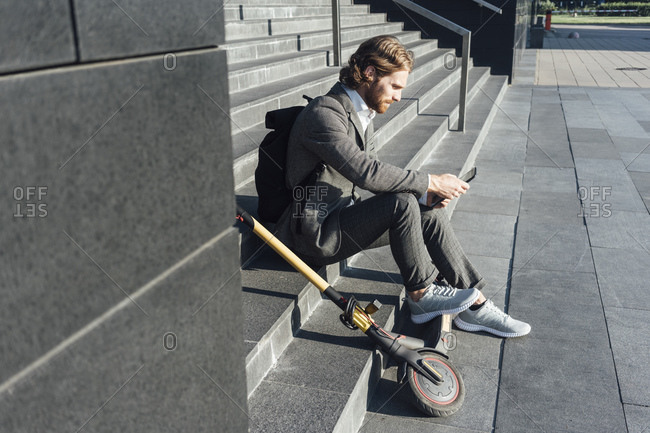 Male commuter using digital tablet while sitting with electric push scooter on steps at downtown