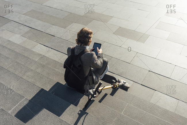 Young entrepreneur using digital tablet while sitting with electric push scooter on steps at downtown during sunny day