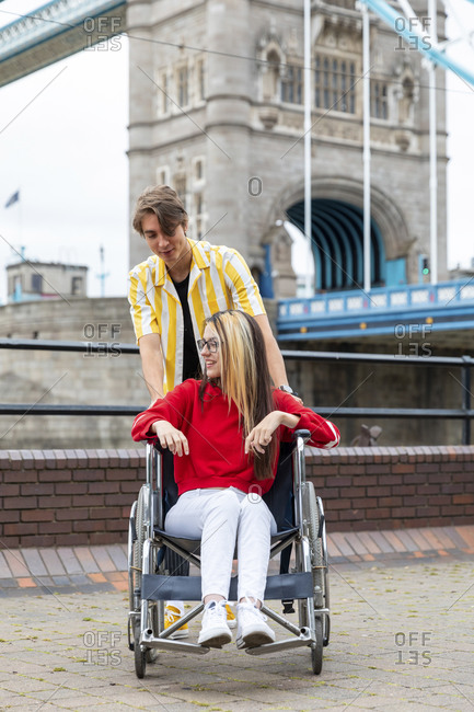 Young man spending leisure time with disabled female friend during weekend- London- UK
