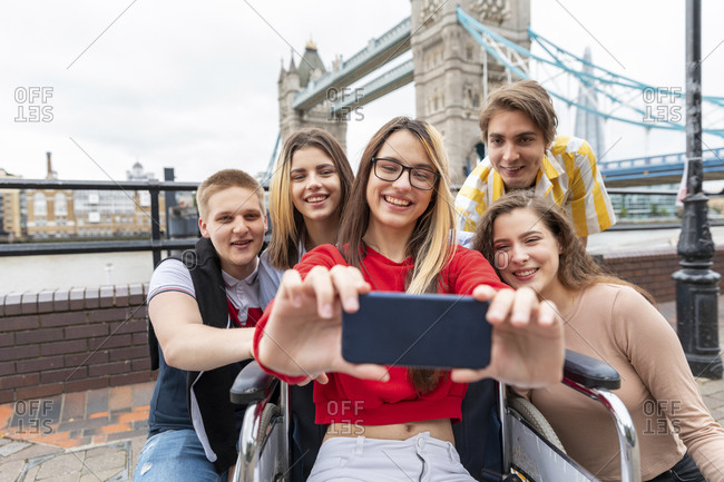 Happy young women and men taking selfie with Tower Bridge in background- London- UK
