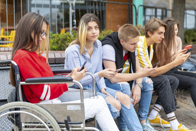 Young woman with friends busy in using smart phones while sitting outdoors