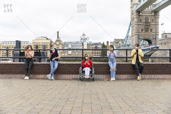 Friends maintaining safe distance and using mobile phones with Tower Bridge in background- London- UK