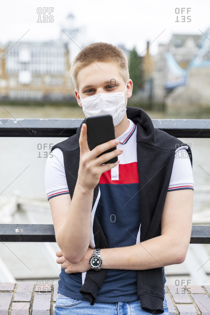 Young man wearing face mask while using smart phone in city during coronavirus outbreak