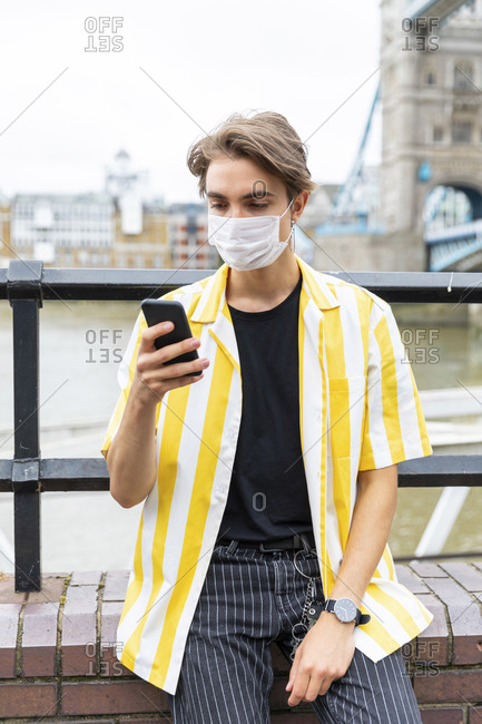 Man wearing face mask while using mobile phone in city during coronavirus outbreak