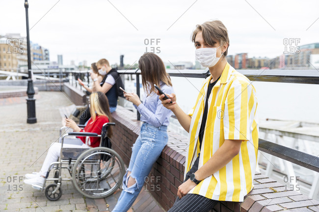 Young man keeping safe distance with friends while using mobile phones in city