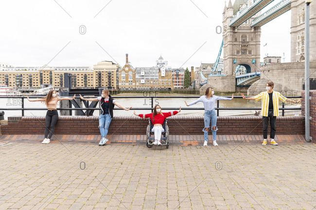 Friends with arms outstretched maintaining safe distance in city- London- UK