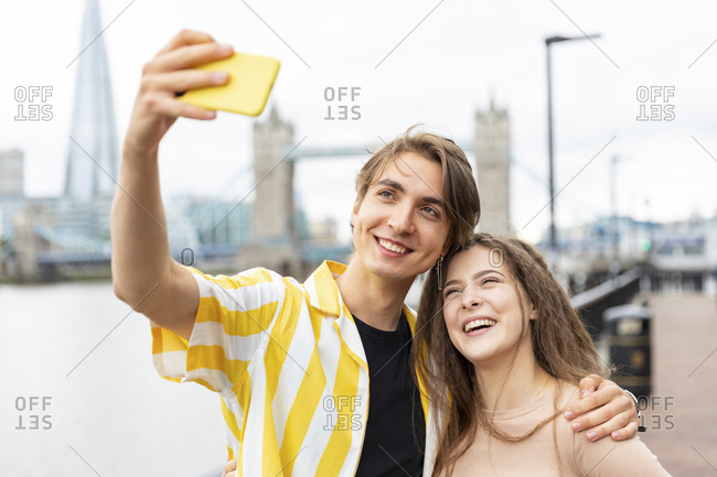 Happy young couple taking selfie with Tower Bridge in background- London- UK