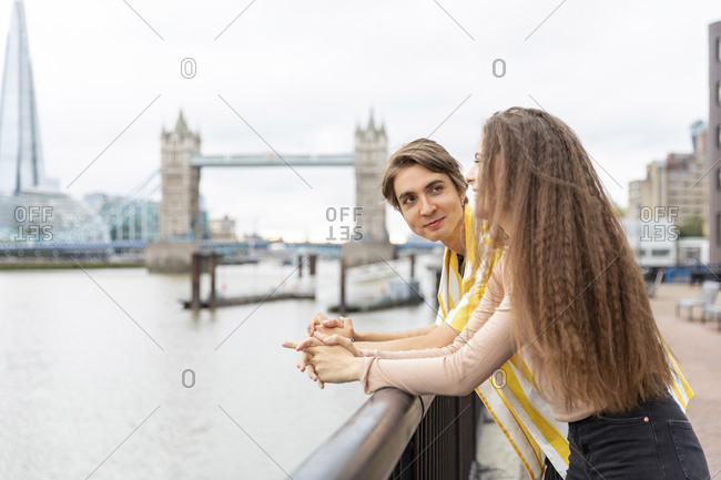Smiling boyfriend and girlfriend leaning on railing in city- London- UK