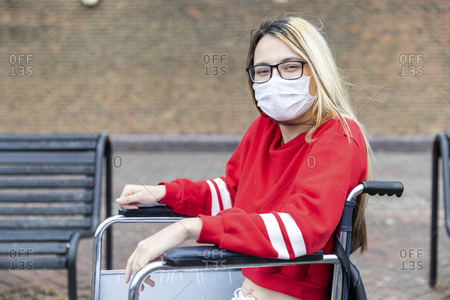 Disabled woman on wheelchair wearing face mask during coronavirus outbreak