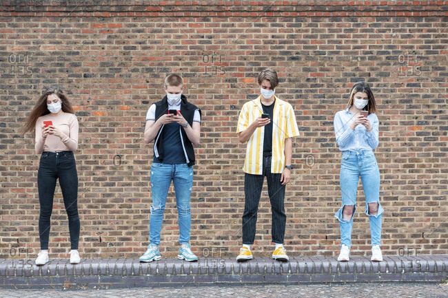 Friends maintaining safe distance while using mobile phones against brick wall in city