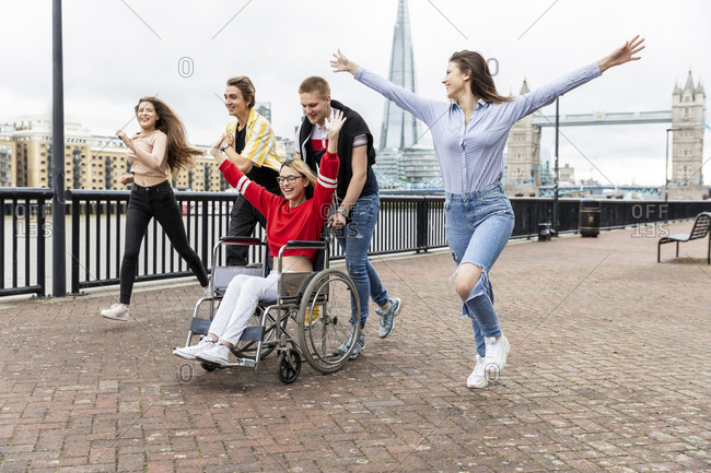 Carefree men and women with disabled female friend spending leisure time in city- London- UK