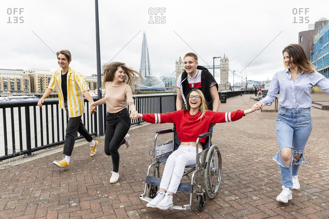 Cheerful men and women with disabled female friend enjoying in city- London- UK