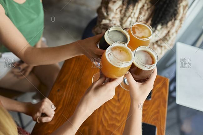 Female friends clinking craft beer glasses in a pub