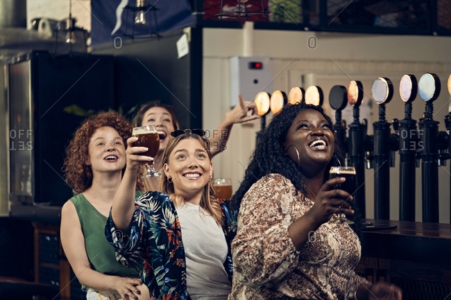 Excited female friends sitting at the counter in a pub watching Tv