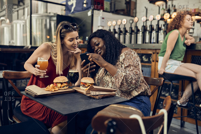 Happy female friends with smartphone having burgers in a pub