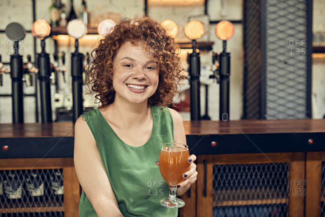 Portrait of a smiling woman in a pub having a beer
