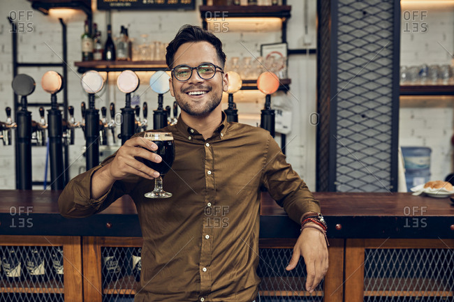 Portrait of a smiling man raising his beer glass in a pub