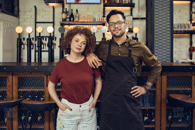 Portrait of confident owner couple at the counter in a pub