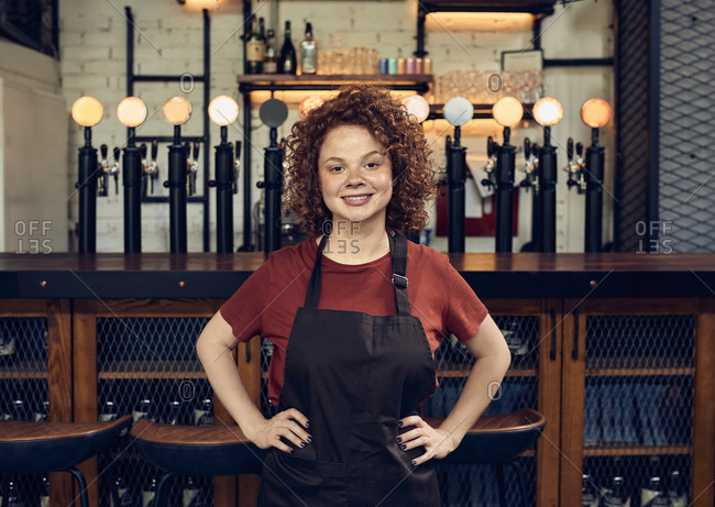 Portrait of a confident waitress at the counter in a pub