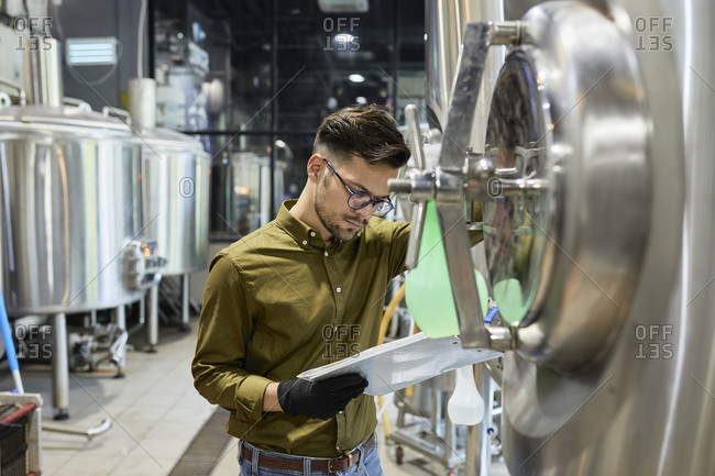 Man working in craft brewery checking clipboard