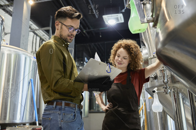 Man and woman working in craft brewery checking document