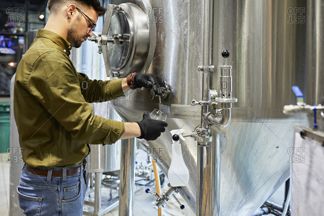 Man working in craft brewery tapping beer from tank