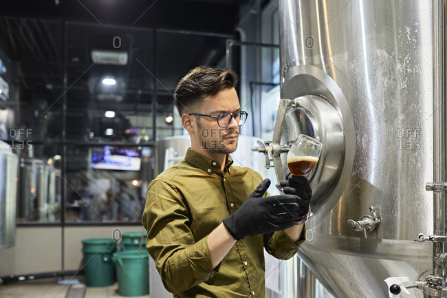 Man working in craft brewery checking quality of a beer