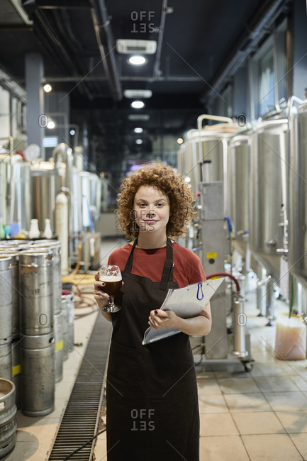 Portrait of confident woman holding clipboard and beer glass in craft brewery