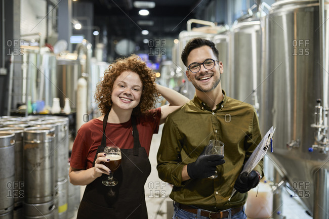 Portrait of happy man and woman holding clipboard and beer glass in craft brewery
