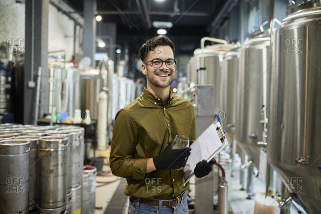 Portrait of happy man holding clipboard and beer glass in craft brewery