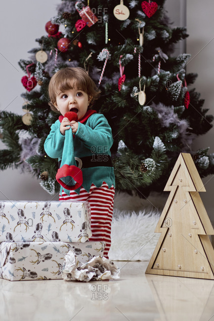A little 12-month-old christmas elf with a christmas tree and gifts