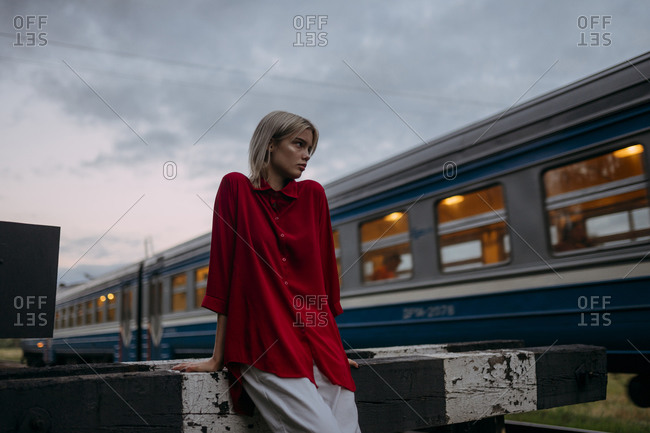 A blonde woman in a red shirt stands near a passing train
