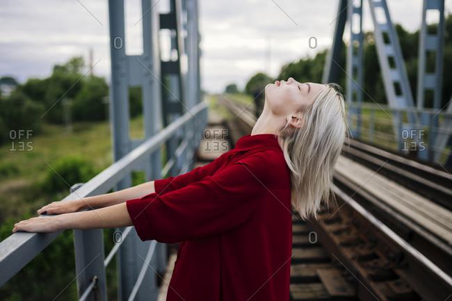 Blond woman on railway bridge