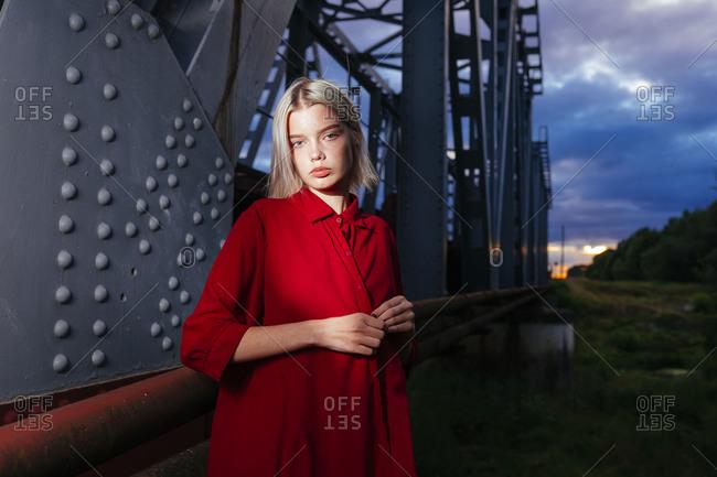 Woman in red standing near railway bridge
