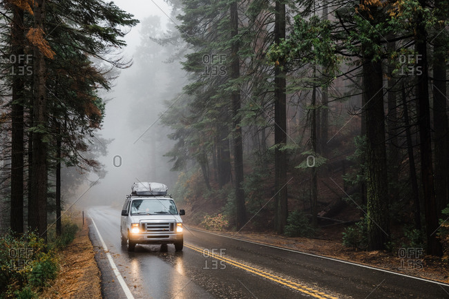 Van drives through wet and foggy autumn forest